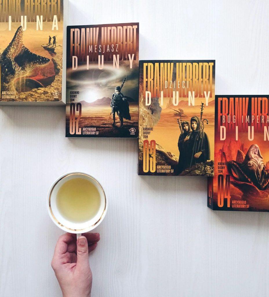 dłoń zfiliżanką herbaty obok rzędu pomarańczowych książek rozłożonych nabiałym stole – tomów 1-4 Kronik Diuny