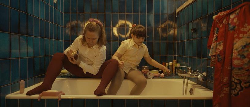 Dwie dziewczynki ubrane siedzą wwannie ibawią się kosmetykami. Kadr zfilmu <em>Zupa nic</em>, reż. Kinga Dębska, 2021.