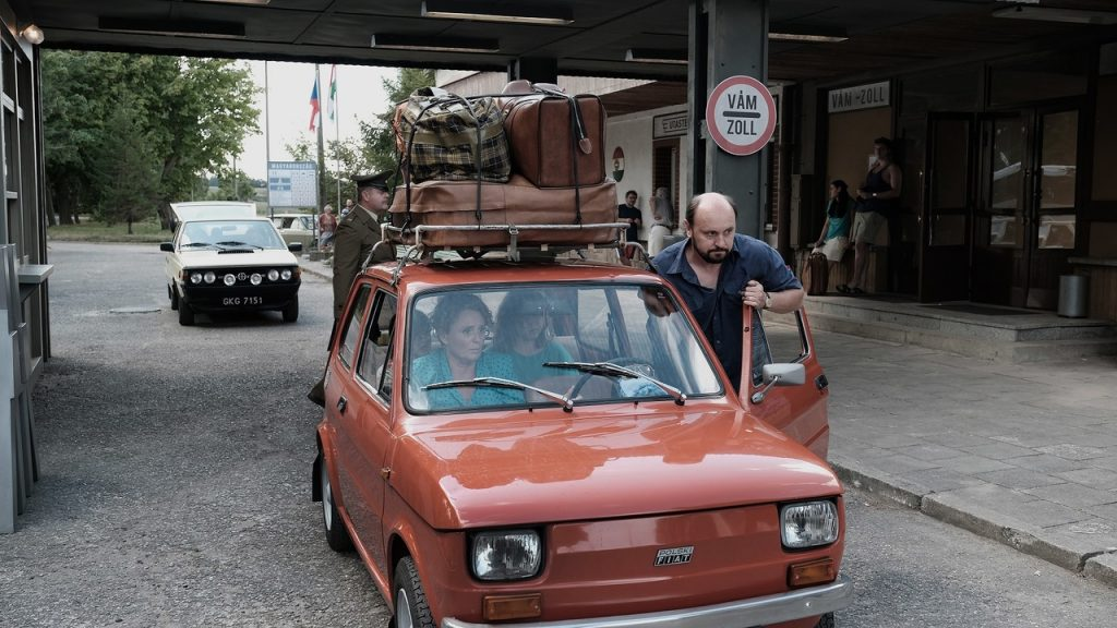 Mężczyzna pcha Fiata 126p przezprzejście graniczne. Kadr zfilmu <em>Zupa nic</em>, reż. Kinga Dębska, 2021.