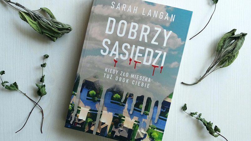 """Książka """"Dobrzy sąsiedzi"""" widziana z góry, na białej powierzchni w otoczeniu suszonych roślin"""